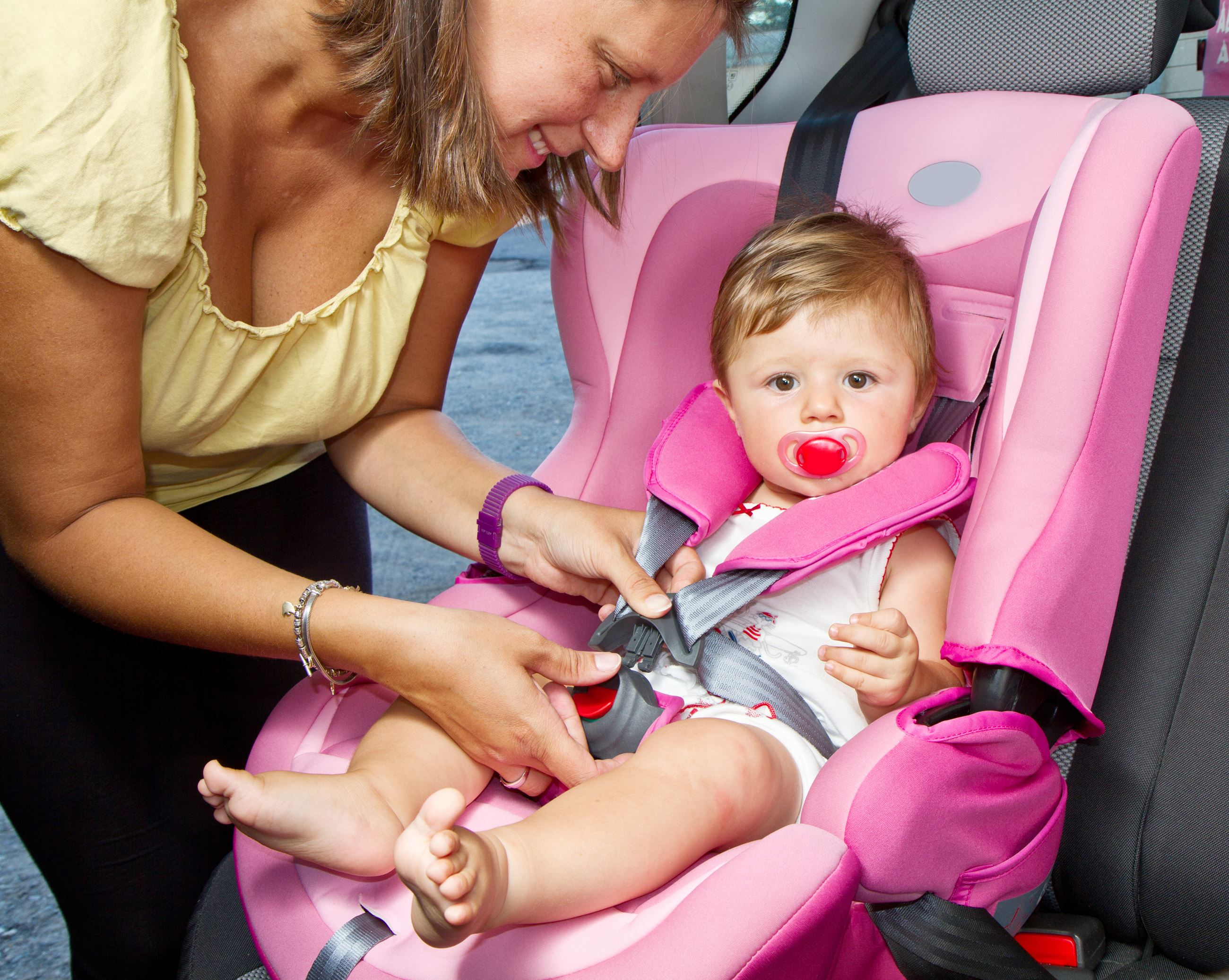 mother strapping toddler into pink car seat